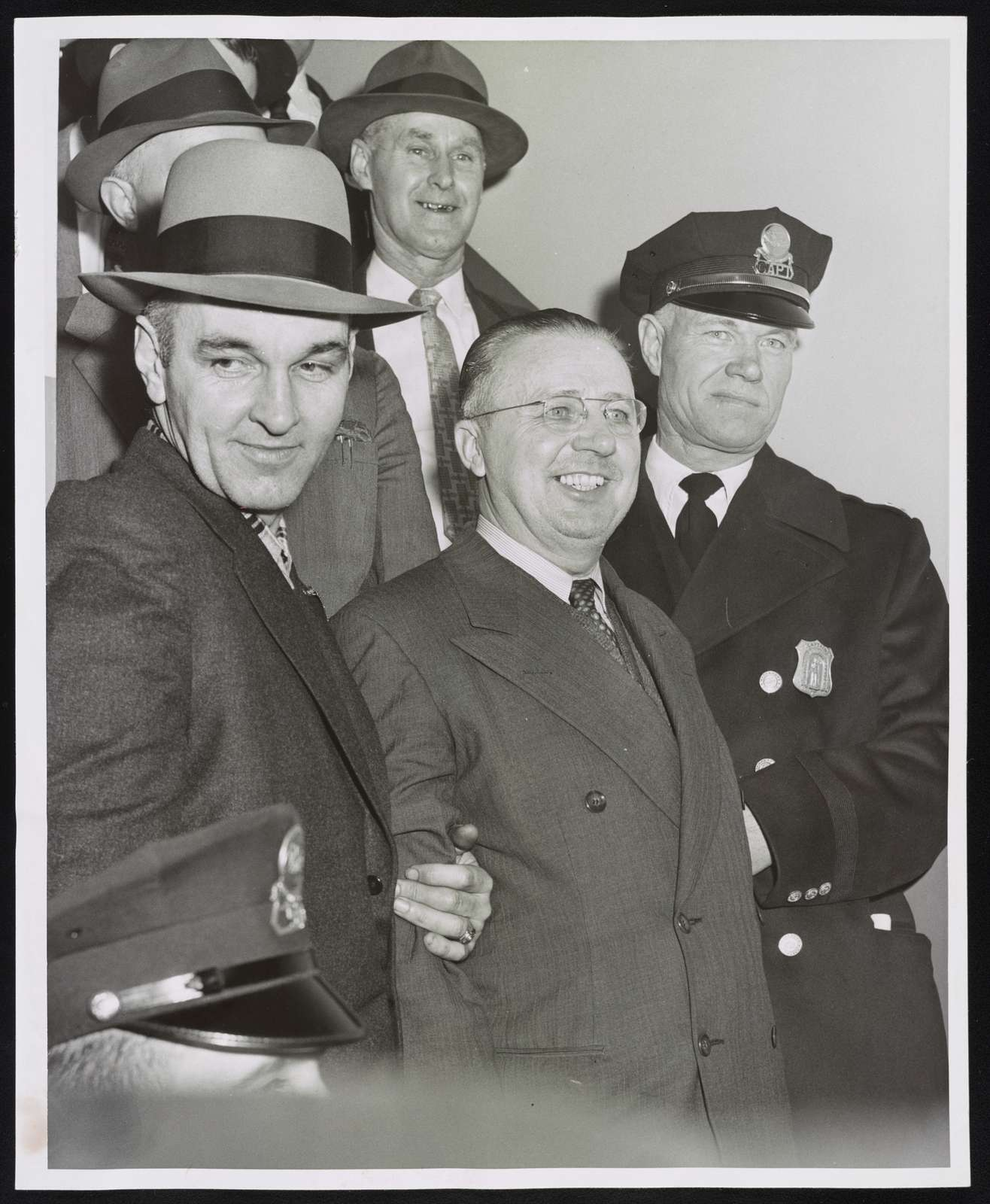 George Metesky being brought from second to first floor to Waterbury police hqs. to be booked Flanking Metesky are Det. Mike Lynch (left) from 24th Sqd., N.Y., and Capt. Ernest Pakul of Waterbury police World Telegram & Sun photo by Phil Stanziola