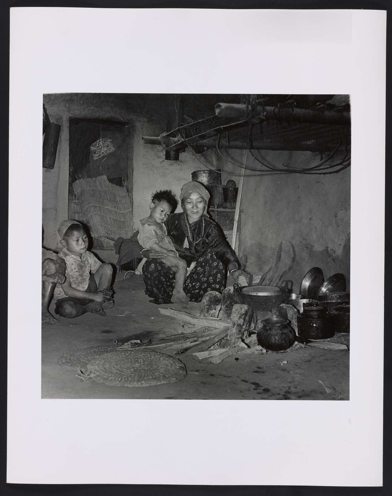 At home, mother cooks dinner at the hearth made from 3 stones