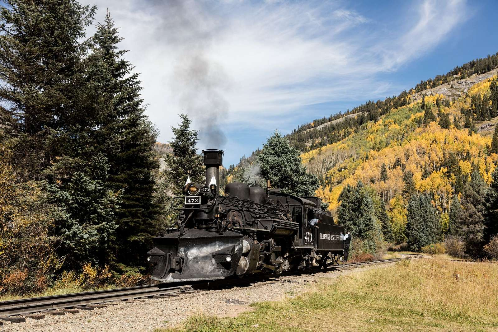 A Durango & Silverton Narrow-Gauge Scenic Railroad train, pulled by a vintage steam locomotive, chugs through the San Juan Mountains in the Colorado county of the same name