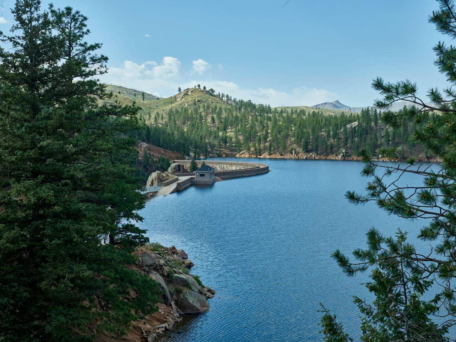 A view of Cheesman Reservoir and a bit of the curve of Cheesman Dam, one of the dams that slows and captures water from the South Platte River for use as part of Denver's drinking-water supply. The dam, which, like the reservoir, was named for Walter Scott Cheesman, a Denver druggist, railroad builder, and designer of water infrastructure, was the world's tallest at 221 feet when it was completed in 1905
