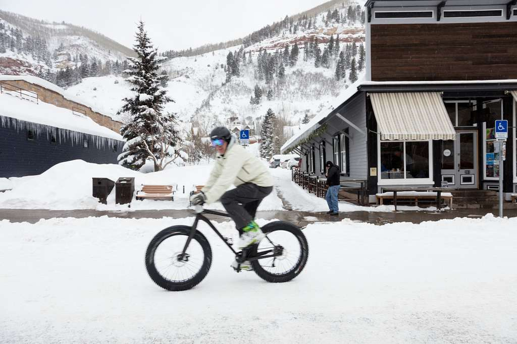 Downtown biker on a day when heavy snow covers the main street of Telluride, Colorado
