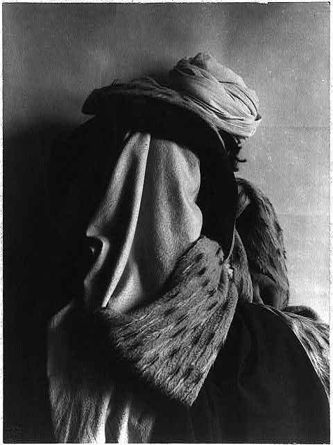 [Person in elaborate costume and turban, three-quarter length, rear view, face turned away]