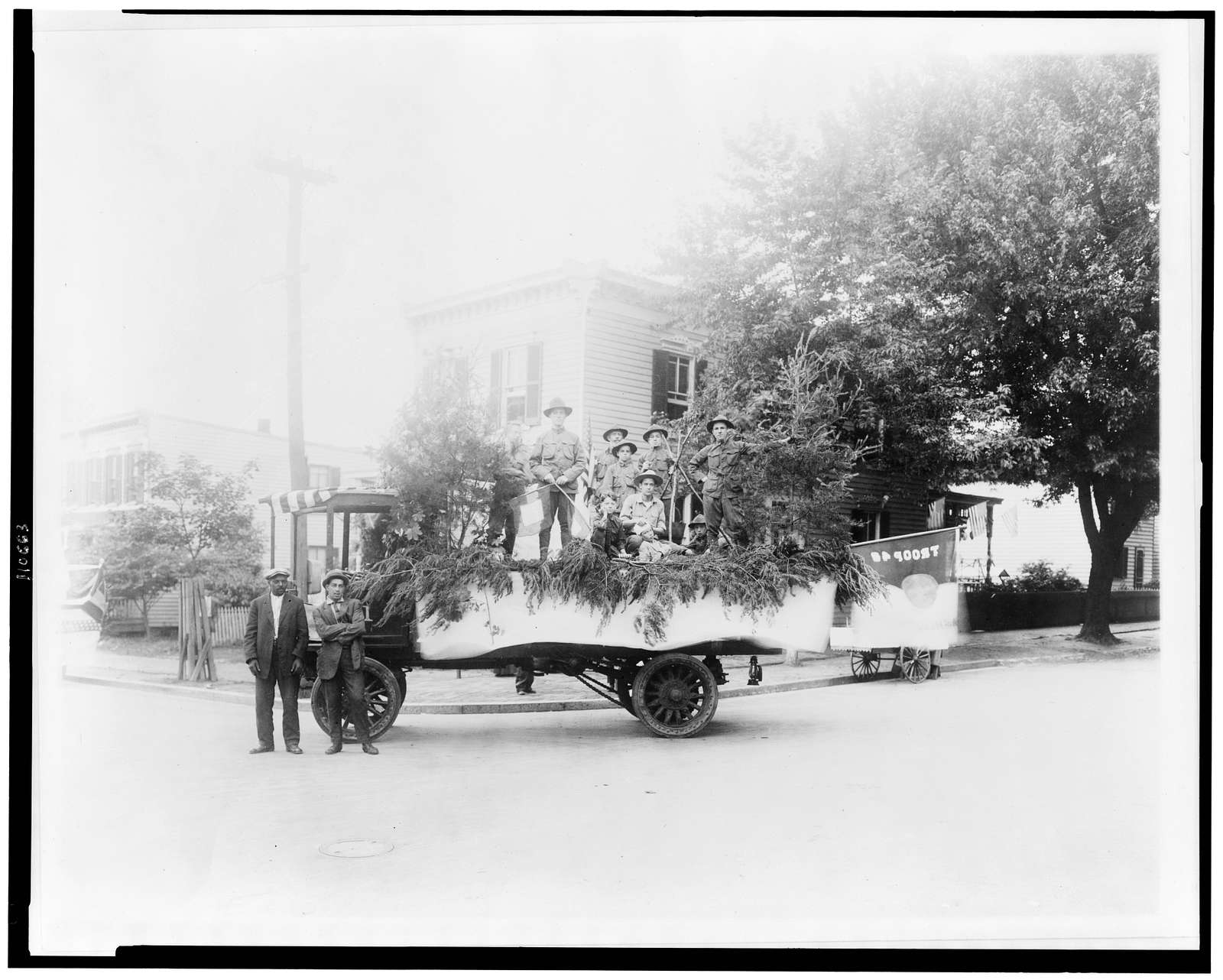 [Boy Scouts posed with a truck decorated for a parade, probably in the Anacostia section of Washington, D.C.]