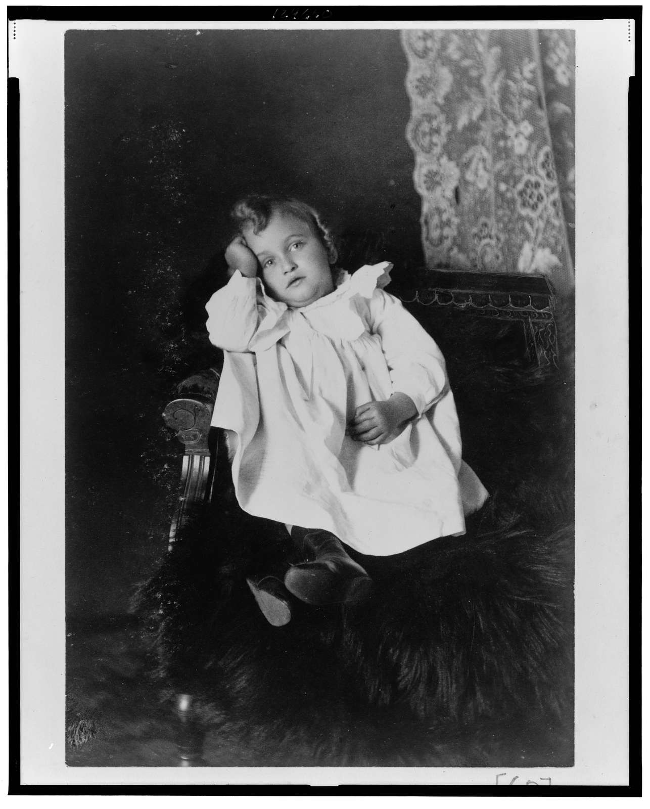 [African American girl, full-length portrait, seated in chair, head resting on right hand, facing front]