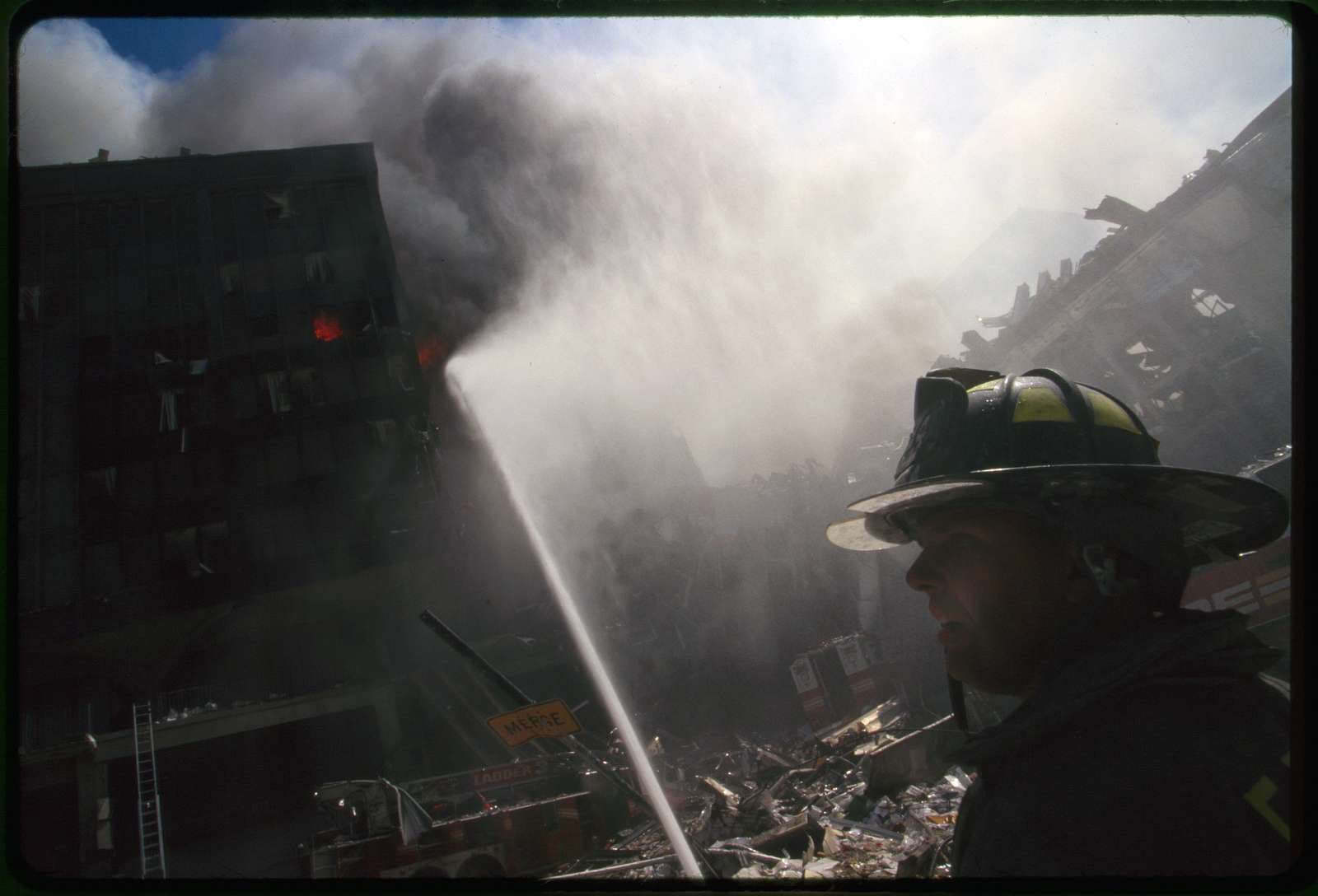 [Fire fighter in front of burning building and rubble following September 11th terrorist attack on World Trade Center, New York City]