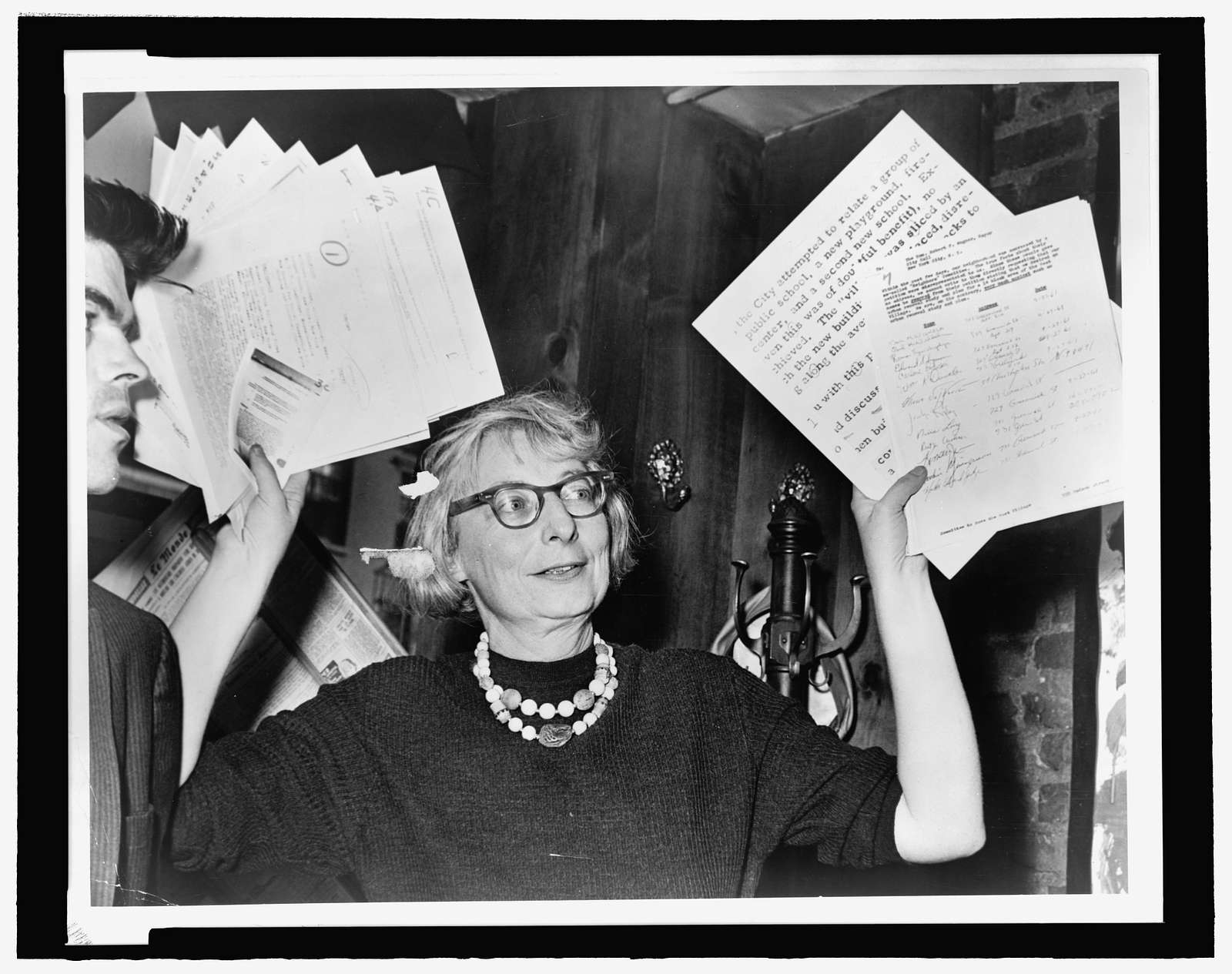 Mrs. Jane Jacobs, chairman of the Comm. to save the West Village holds up documentary evidence at press conference at Lions Head Restaurant at Hudson & Charles Sts / World Telegram & Sun photo by Phil Stanziola.