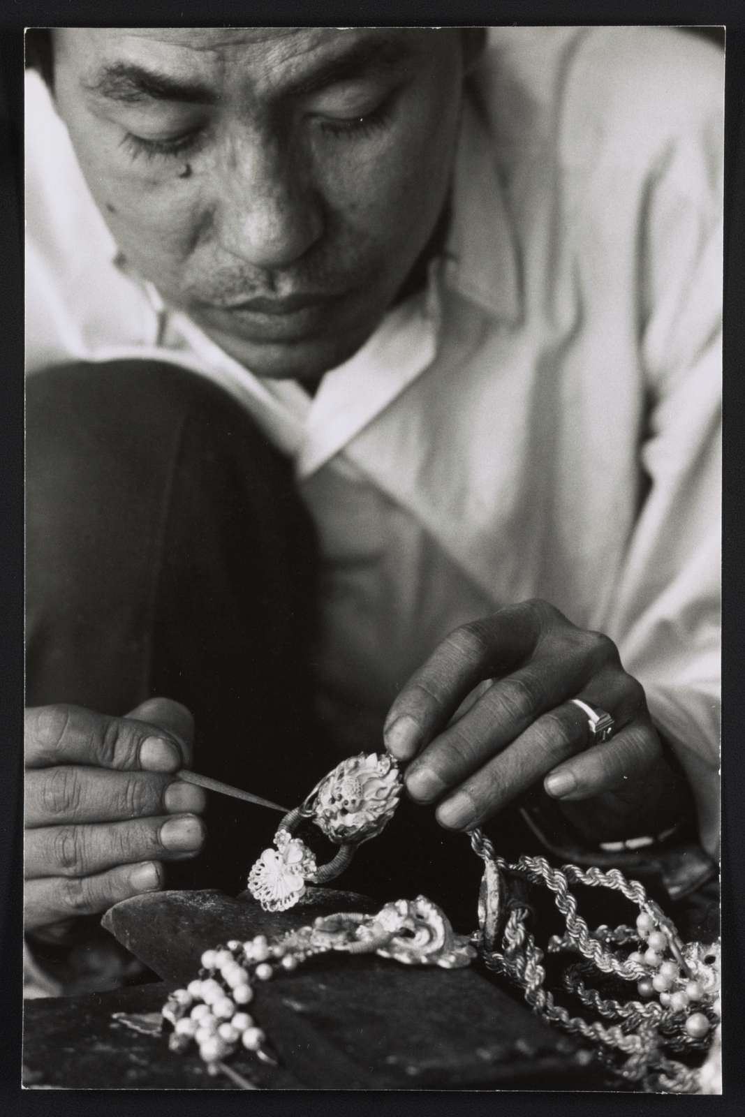 Silversmith hand carves gold necklace
