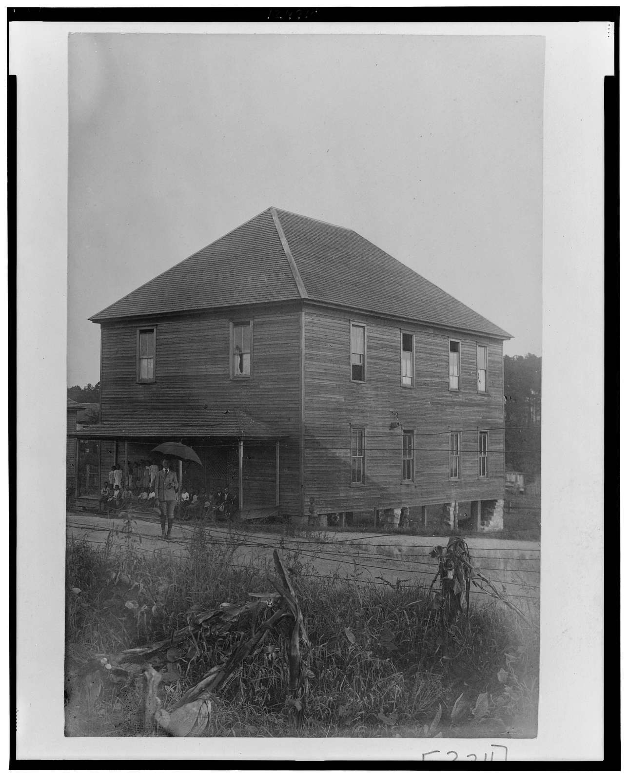 [Exterior view of large unidentified building in Georgia, with a man standing in front holding an umbrella, and a group of children sitting on the porch]