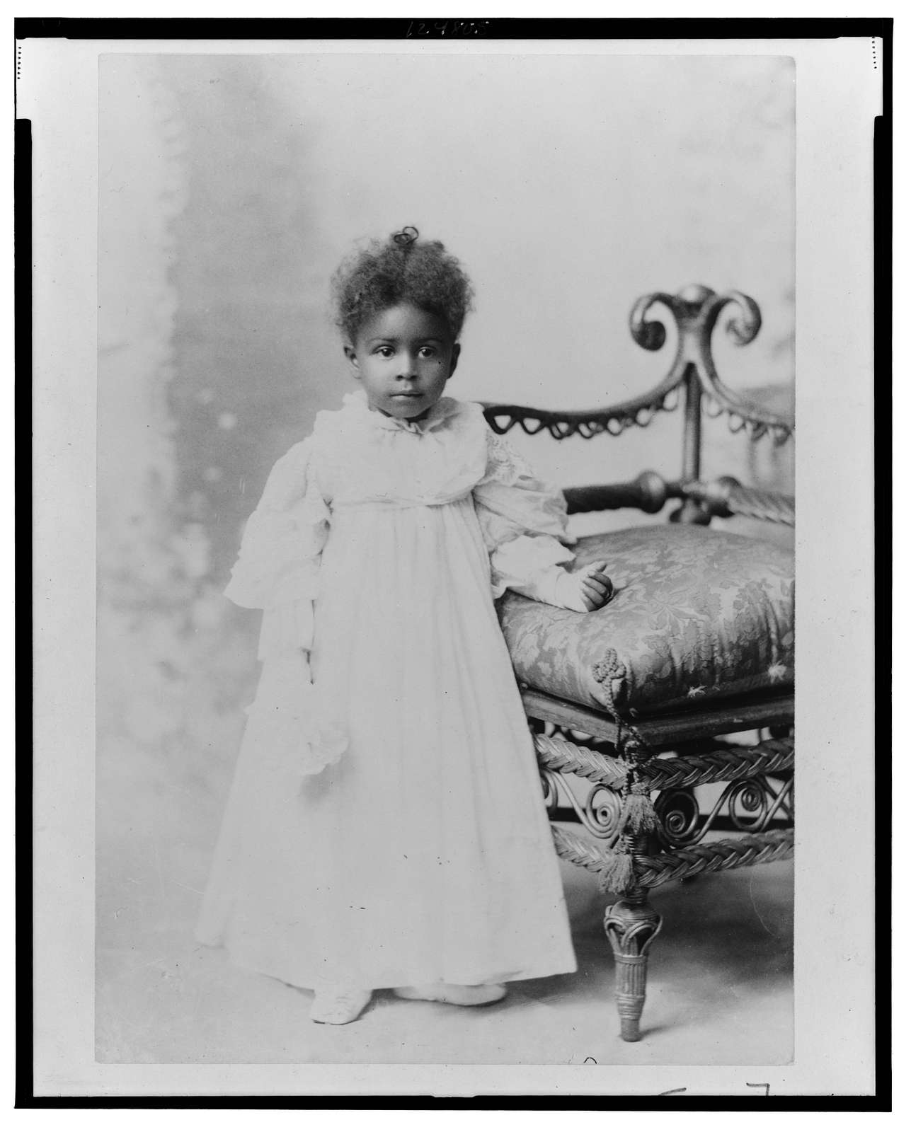 [African American girl, full-length portrait, standing next to chair, facing front]