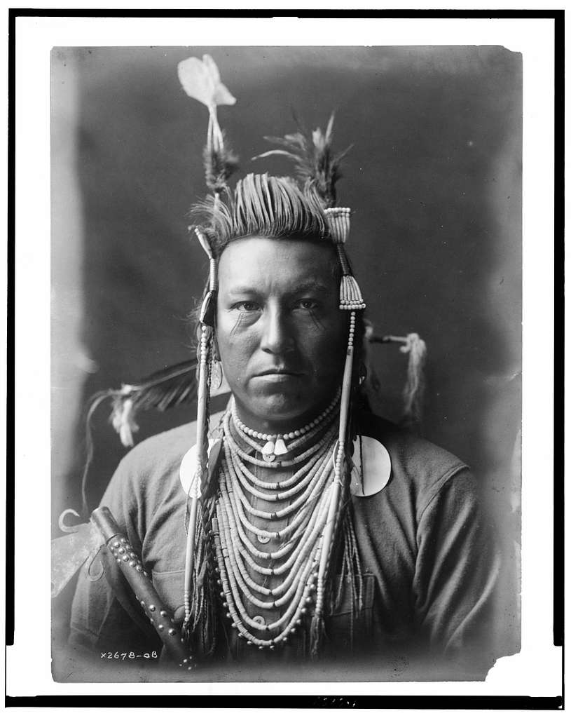 [Swallow Bird, Crow Indian, Montana, head-and-shoulders portrait, facing front, painted pompadour, Apsaroke headdress, flannel shirt, beads on chest, studded pipe held in front of right arm]