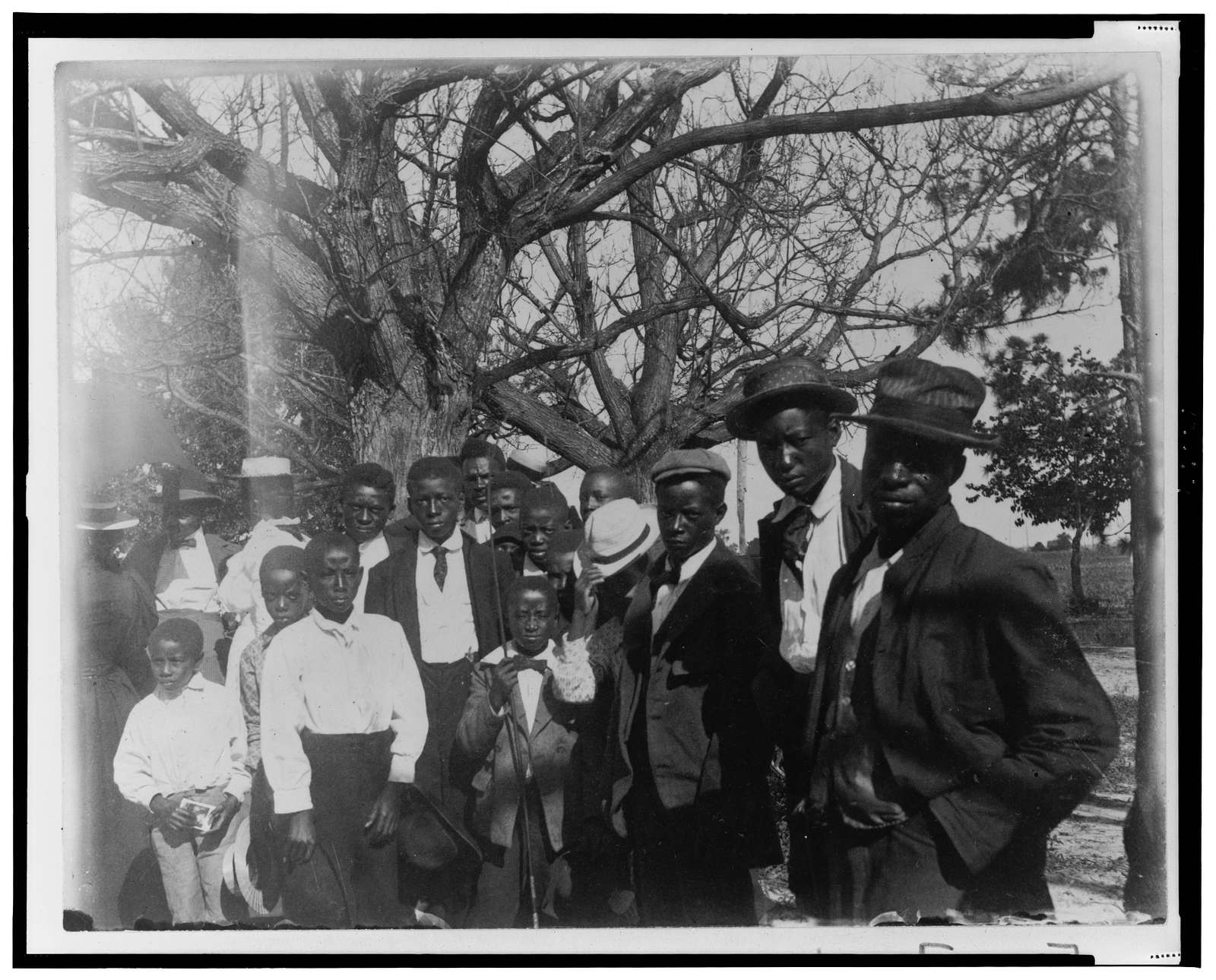 [African American men and boys, three-quarter length portrait, dressed for church, trees in background]