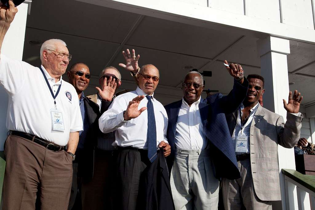 Bob Feller, Ozzie Smith, Bruce Sutter, Reggie Jackson, Hank Aaron and Rickey Henderson wave to the crowd on the porch of Hank Aaron boyhood home at the dedication ceremony at the Hank Aaron Boyhood Home Museum at the Hank Aaron Stadium, Mobile, Alabama
