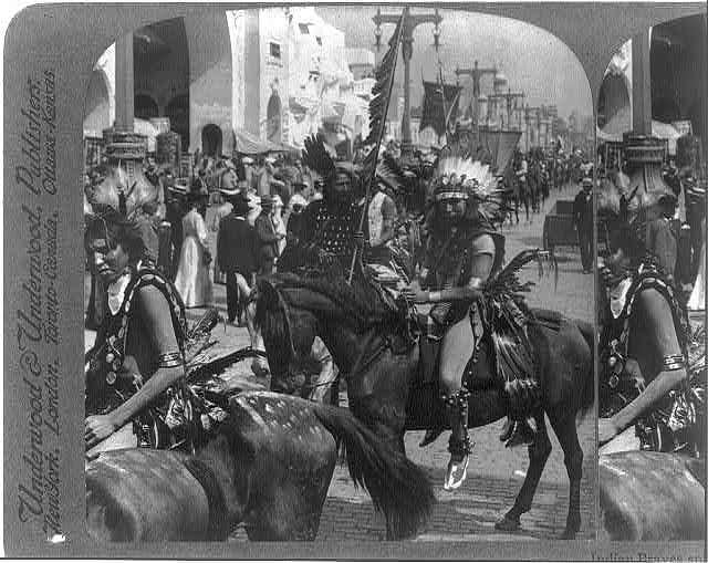 Indian braves, splendid with savage finery, riding their ponies down the Pike, World's Fair, St. Louis