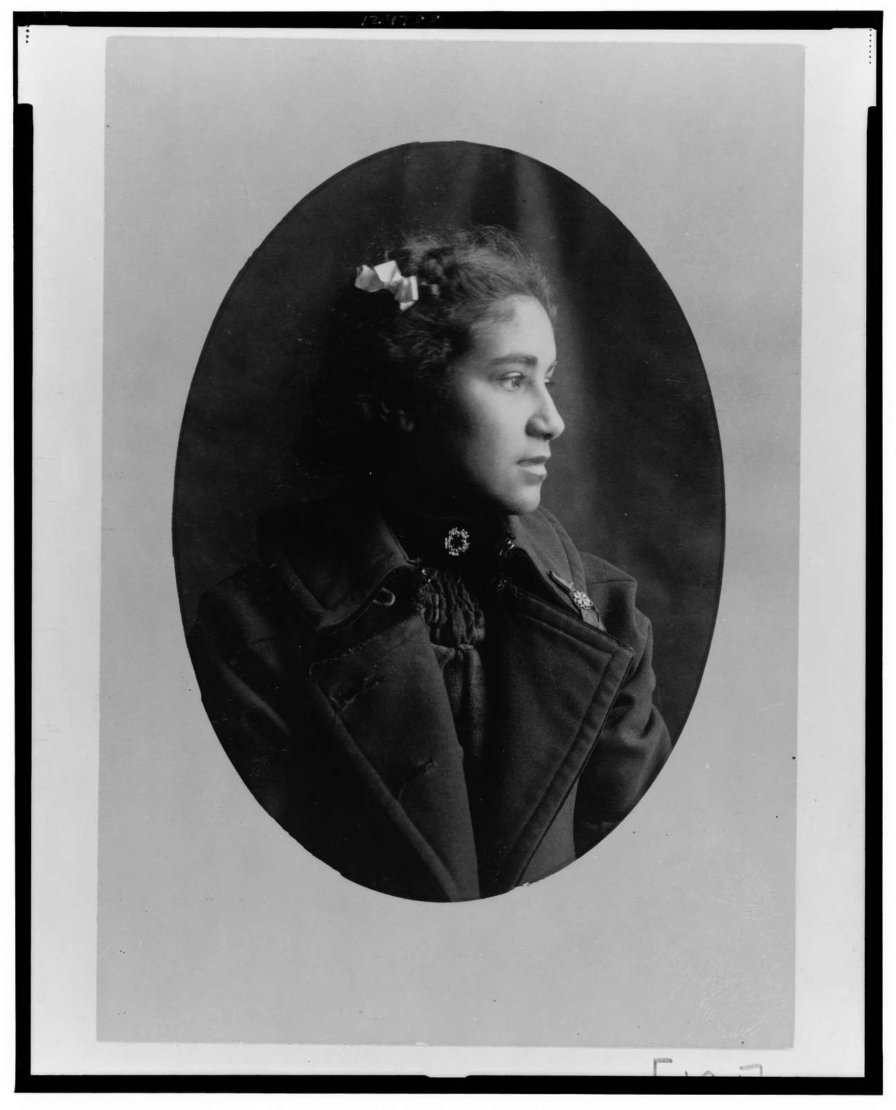 [African American woman, head-and-shoulders portrait, facing right, wearing coat]