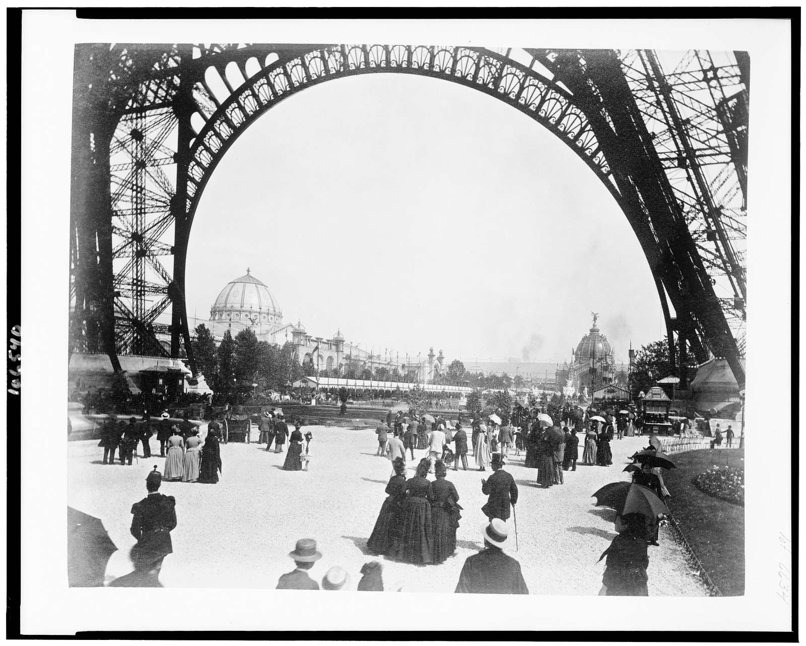 [View of the Palace of Fine Arts on left, and the Central Dome on right, seen through the base of the Eiffel Tower, with people walking under the Tower, Paris Exposition, 1889]