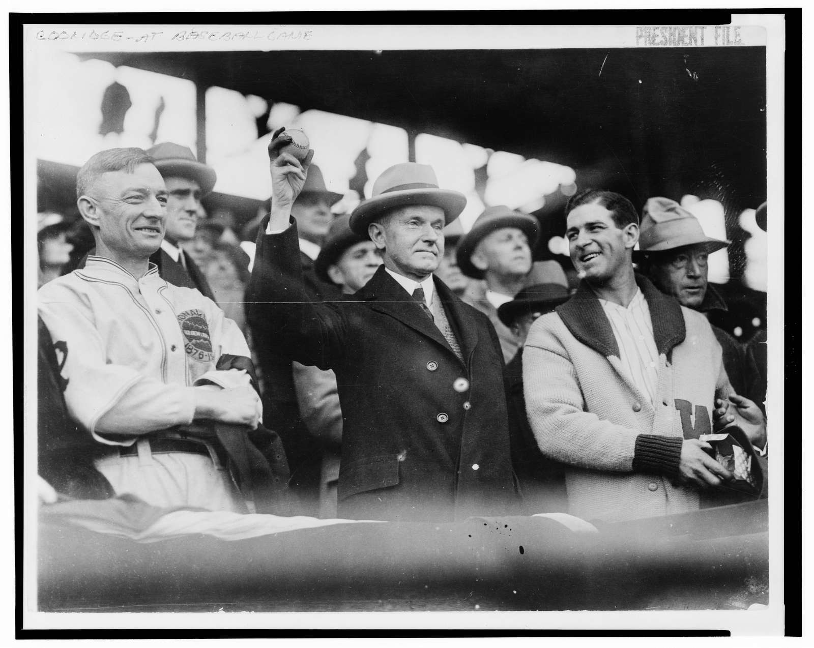 [Calvin Coolidge, half length, standing, facing slightly right, holding up baseball at baseball game prior to opening game, 1925. L.to R.: Bill McKechnie, Coolidge, Bucky Harris]