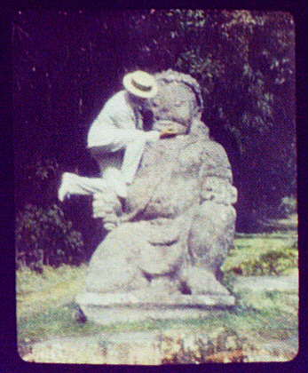 Man in straw hat standing on Buddhist idol at ruins of Borobudur