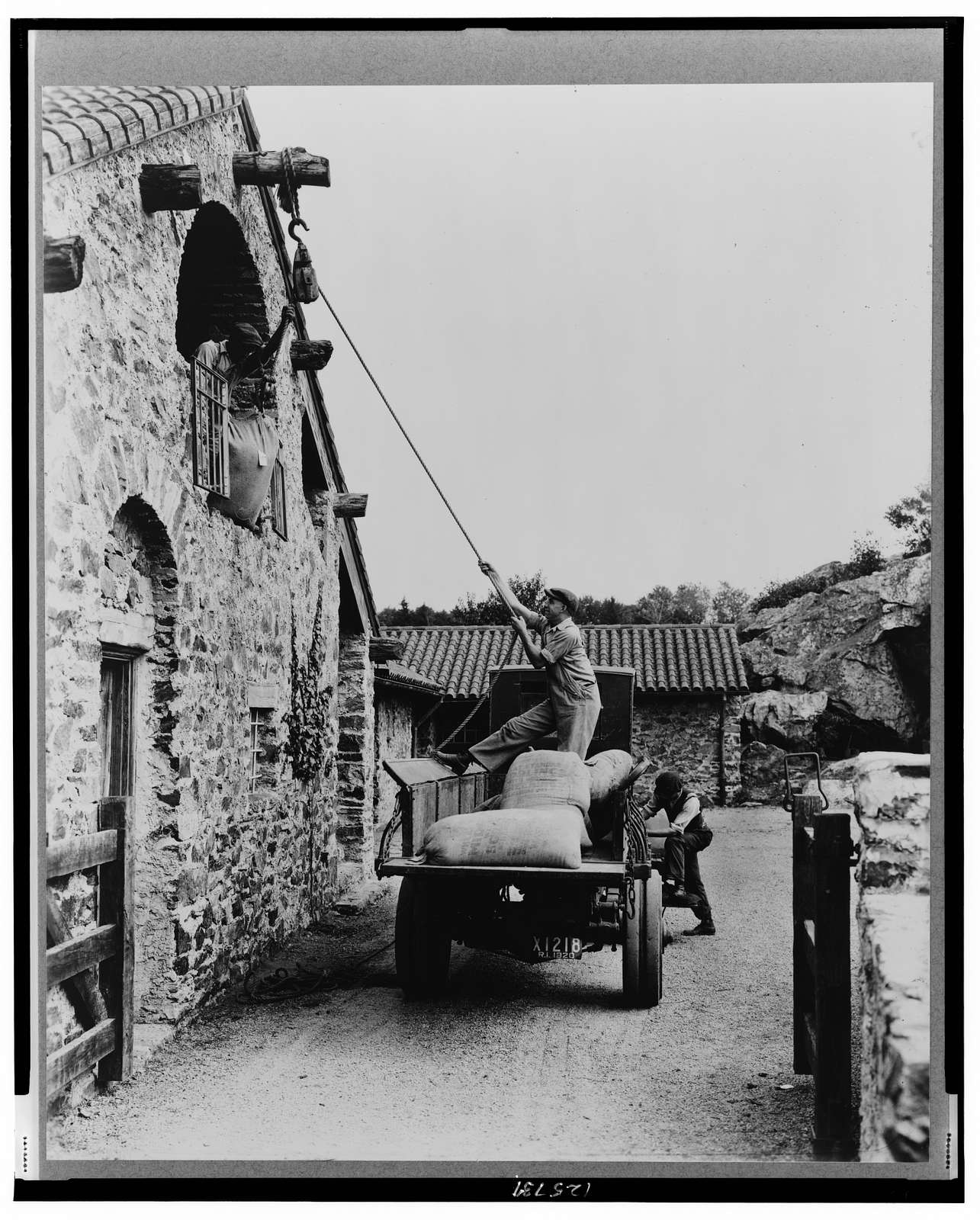 "[""Surprise Valley Farm,"" Arthur Curtiss James property, Beacon Hill Road, Newport, Rhode Island. Men loading sacks of grain from truck in courtyard into second floor doorway of barn]"