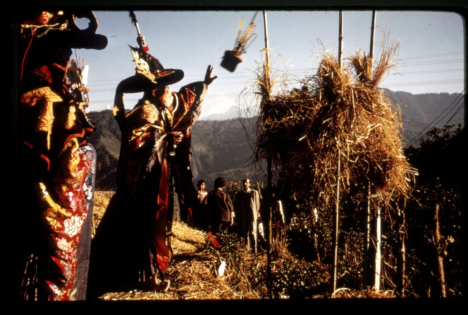 [Black Hat Lama throwing religious sacrifice into fire to destroy evil for the New Year, Sikkim]
