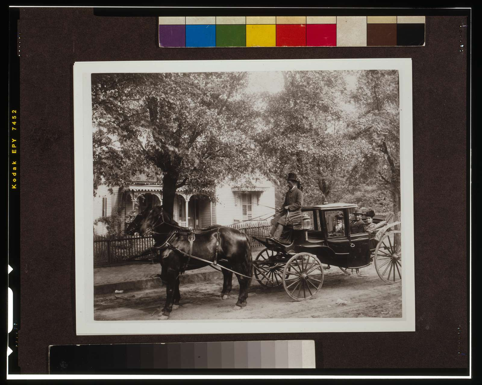 [David Tobias Howard, an undertaker, his mother, and wife, Atlanta, Georgia; seated in a horse-drawn carriage with tree-shaded house in background]