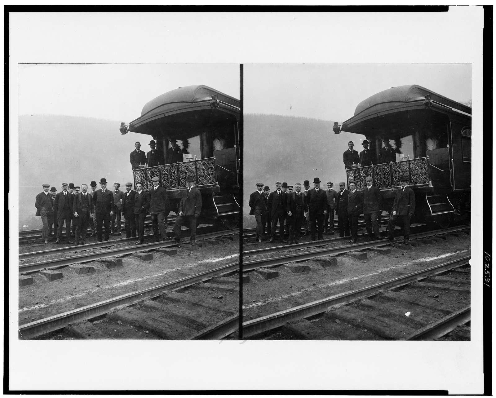 [President Roosevelt, standing with twelve other men on railroad tracks, in front of locomotive]