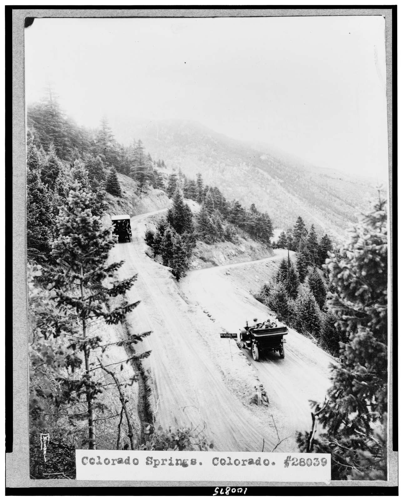 [Colorado Springs, Colorado. Two automobiles going down mountain road, with horseshoe turn in foreground] / Wiswall(?).