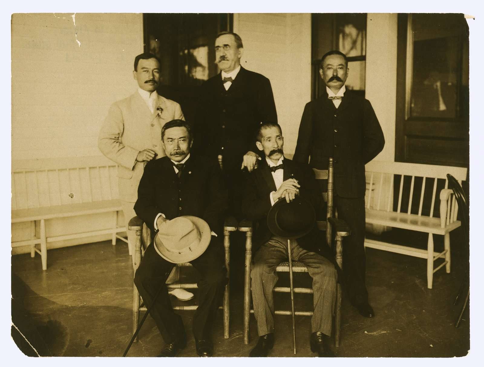 [Japanese envoys Kogoro Takhira (seated, left), Jutarō Komura (seated, right) with two staff members and H.W. Dennison, the American advisor to the Japanese delegation, full-length portrait facing front]
