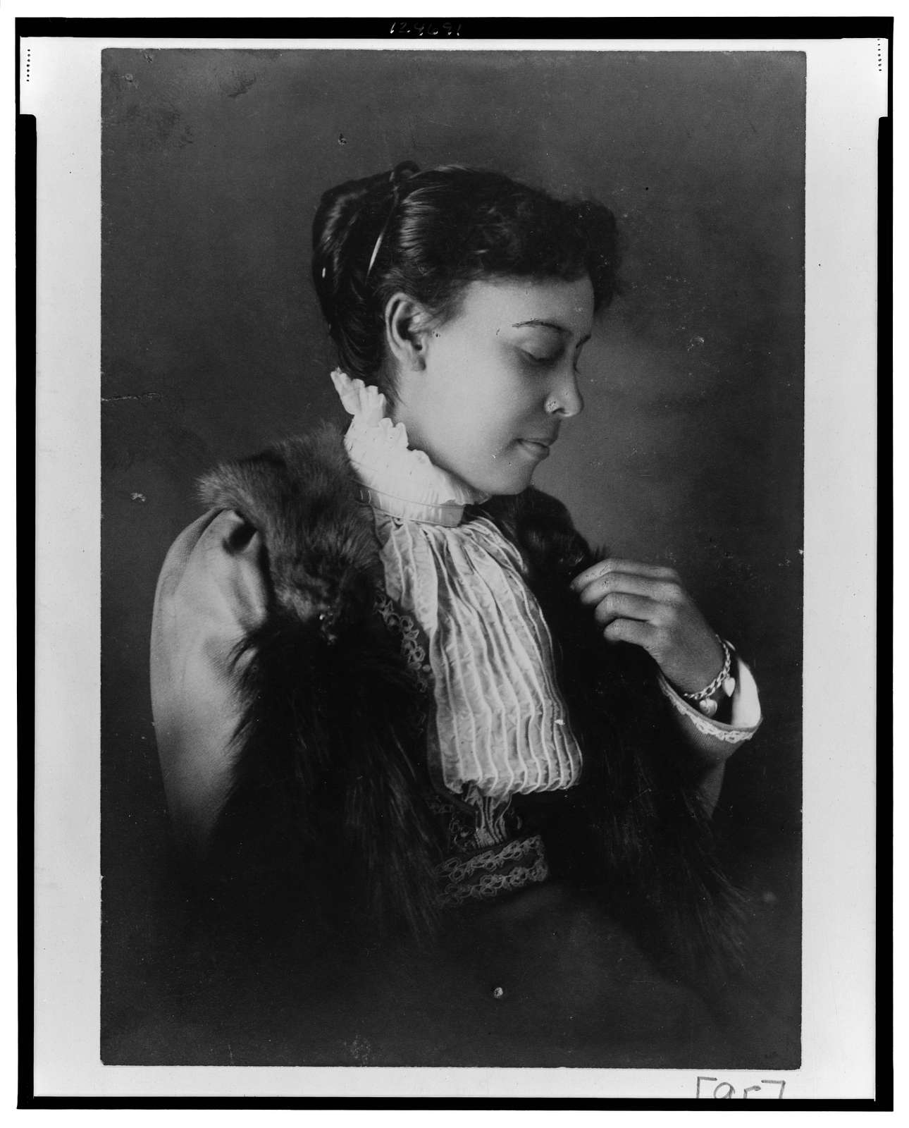 [African American woman, half-length portrait, seated, facing right]