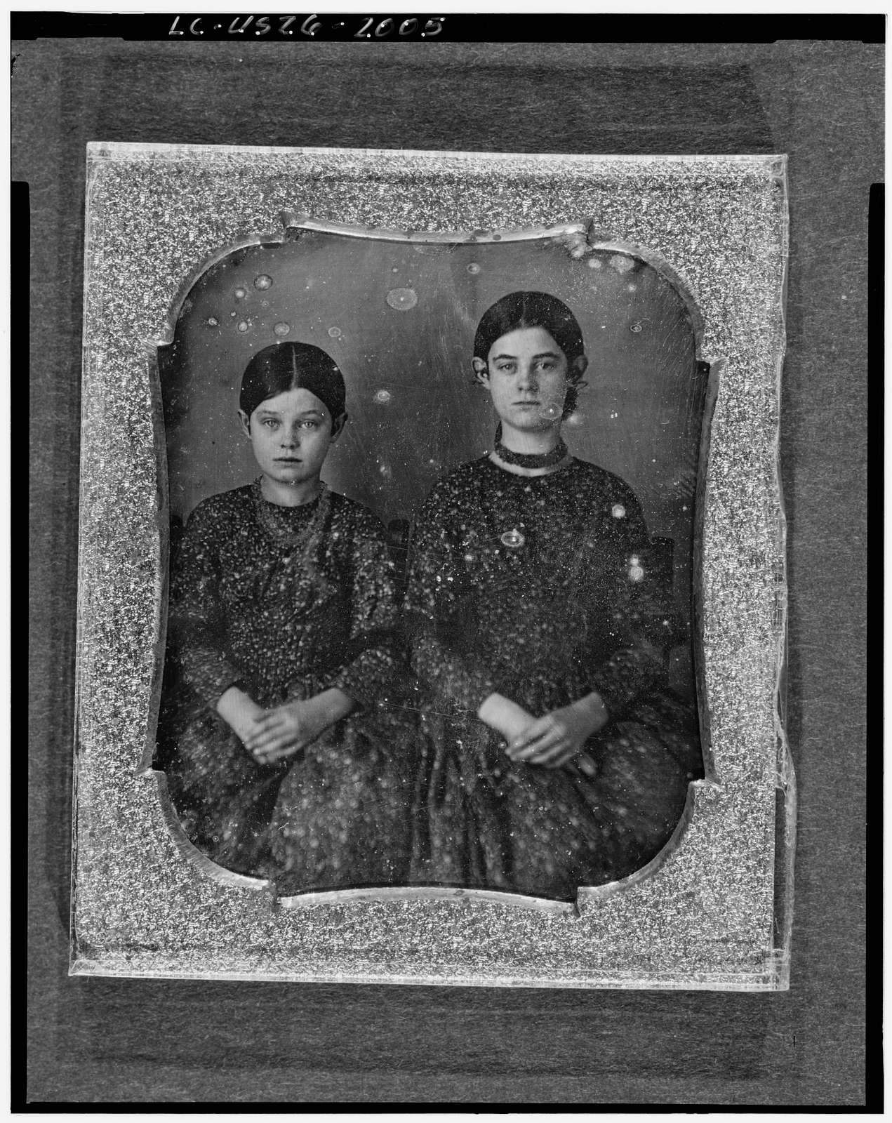 [Group portrait of two unidentified girls, three-quarter length, seated, facing front]