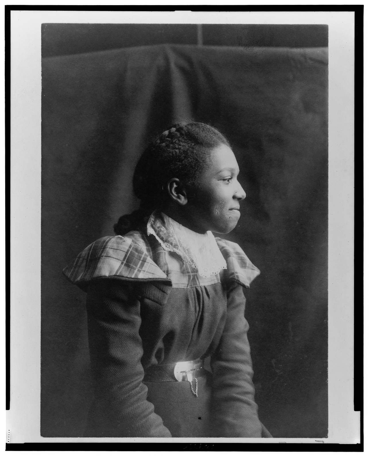 [African American woman, half-length portrait, seated, right profile]
