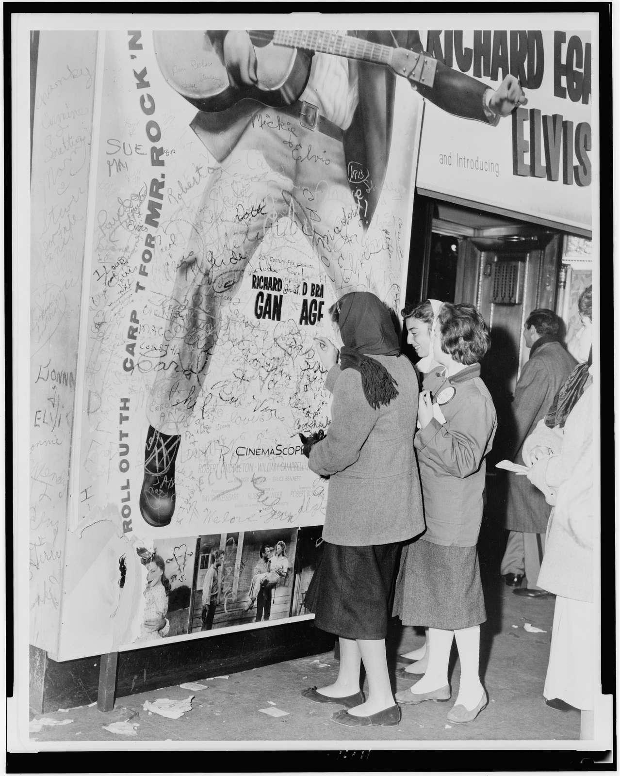 [Teenage girls add to grafitti on bottom of Elvis movie poster] / World Telegram & Sun photo by Phil Stanziola.