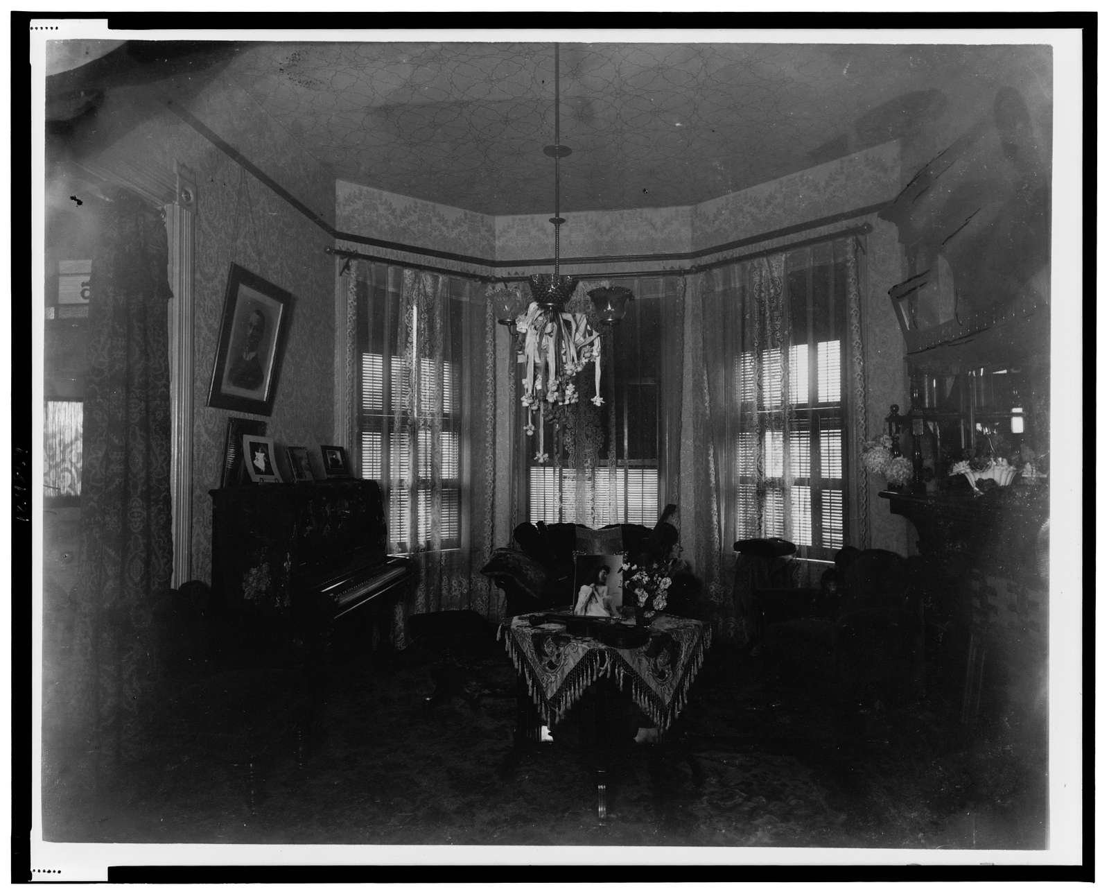 [Interior view of room showing furniture, piano, and chandelier]