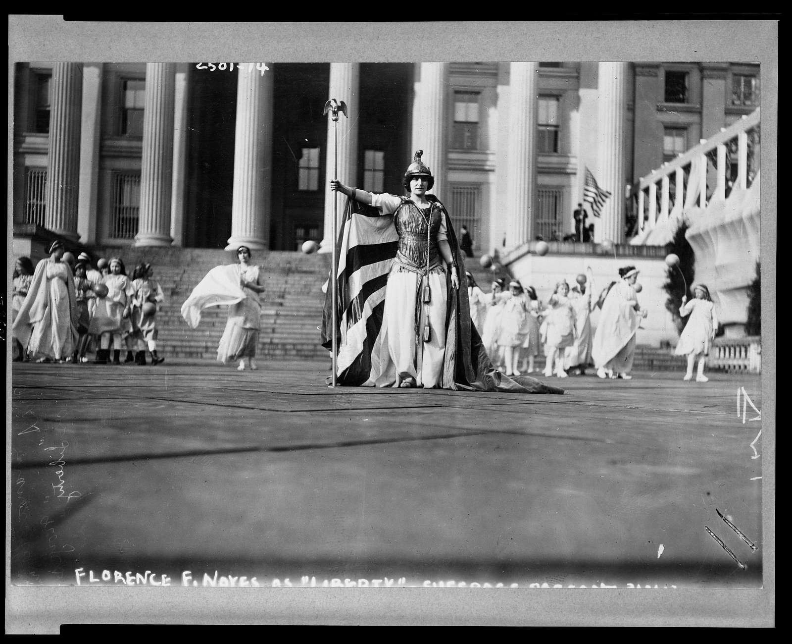 """[German actress Hedwig Reicher wearing costume of """"Columbia"""" with other suffrage pageant participants standing in background in front of the Treasury Building, March 3, 1913, Washington, D.C.]"""