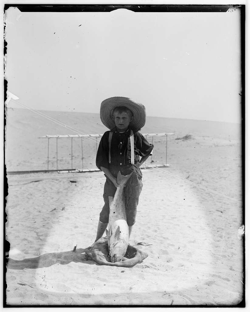[Tom Tate, son of Captain Tate's half-brother Daniel Tate, posing with a drum fish in front of 1900 Wright glider]