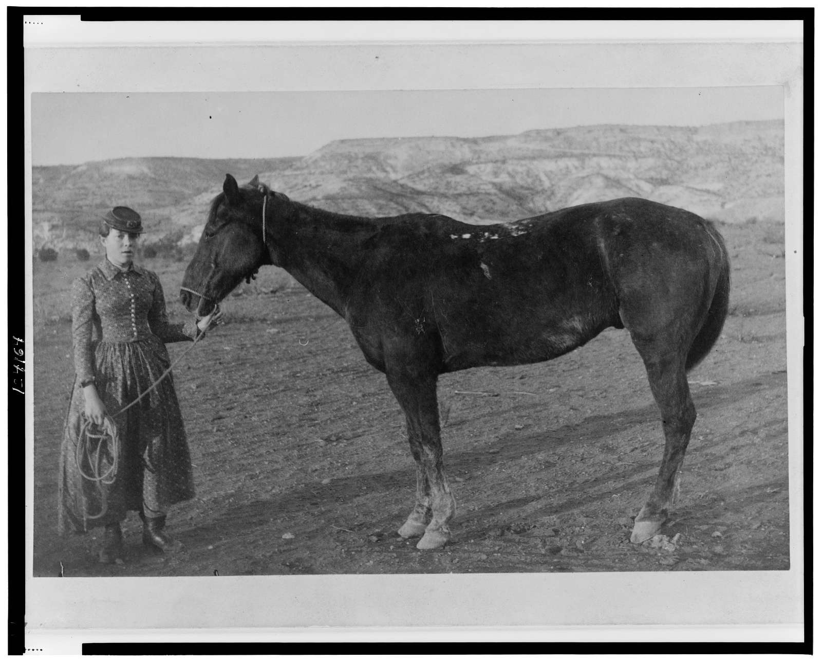[Emma Baldwin(?), daughter of Captain Theodore Baldwin, full-length portrait, standing with her horse, Mex, facing slightly right, Fort Verde, Arizona]