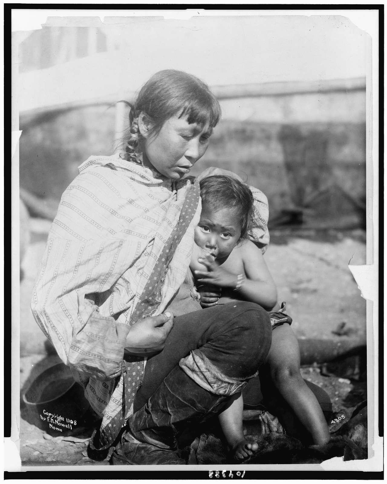 [Inuit Eskimo woman breast-feeding baby]