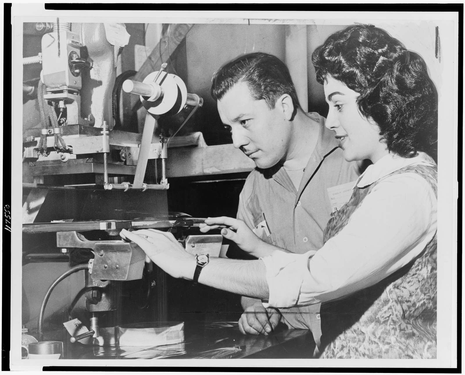 Ralph Lopez, foreman of a transparent box factory, tells Carmen Zapata how to operate a stamping machine / World Telegram & Sun photo by Phil Stanziola.