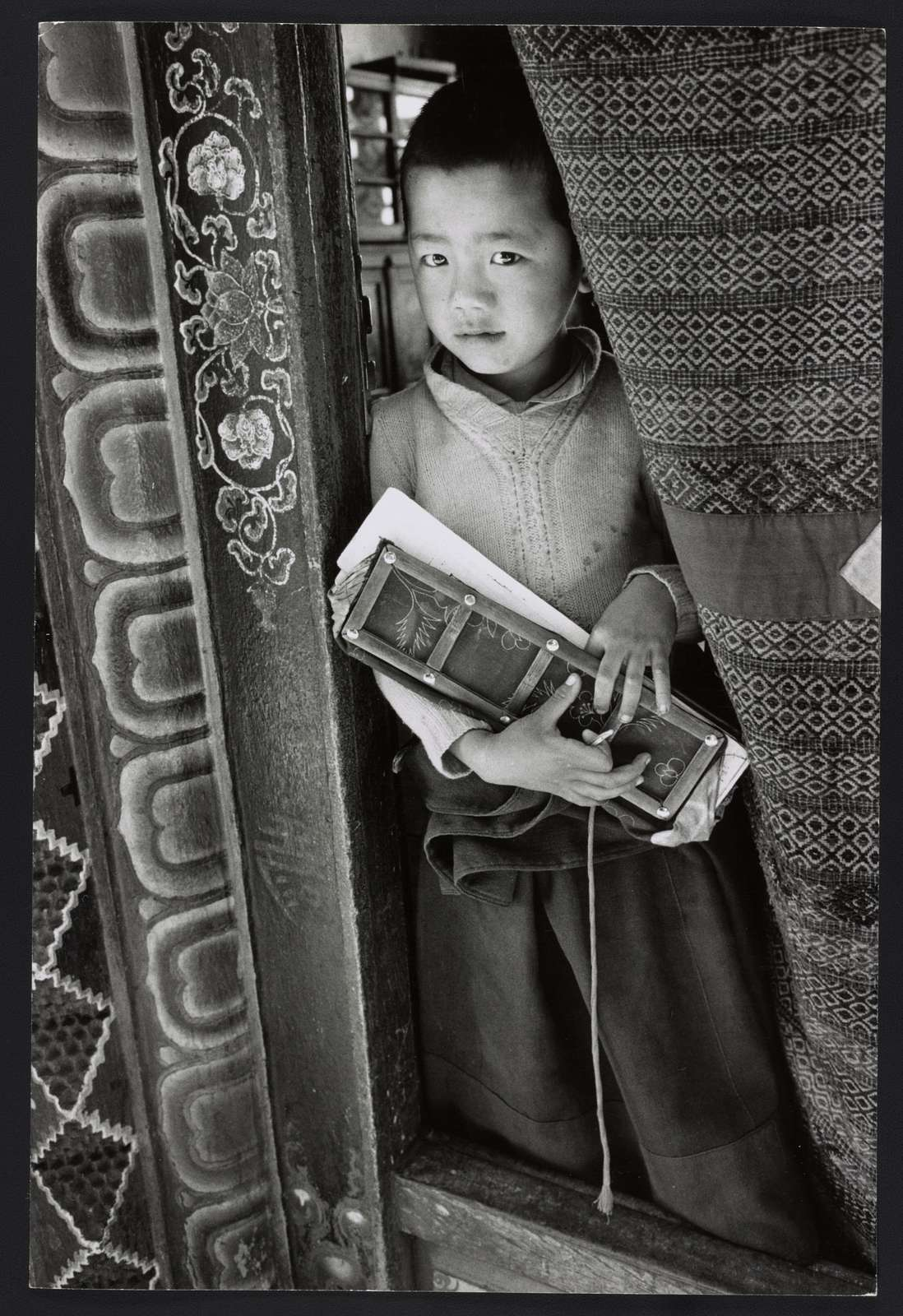 Reincarnation of a holy lama takes a break from his reading. He holds a prayer book covered in wood