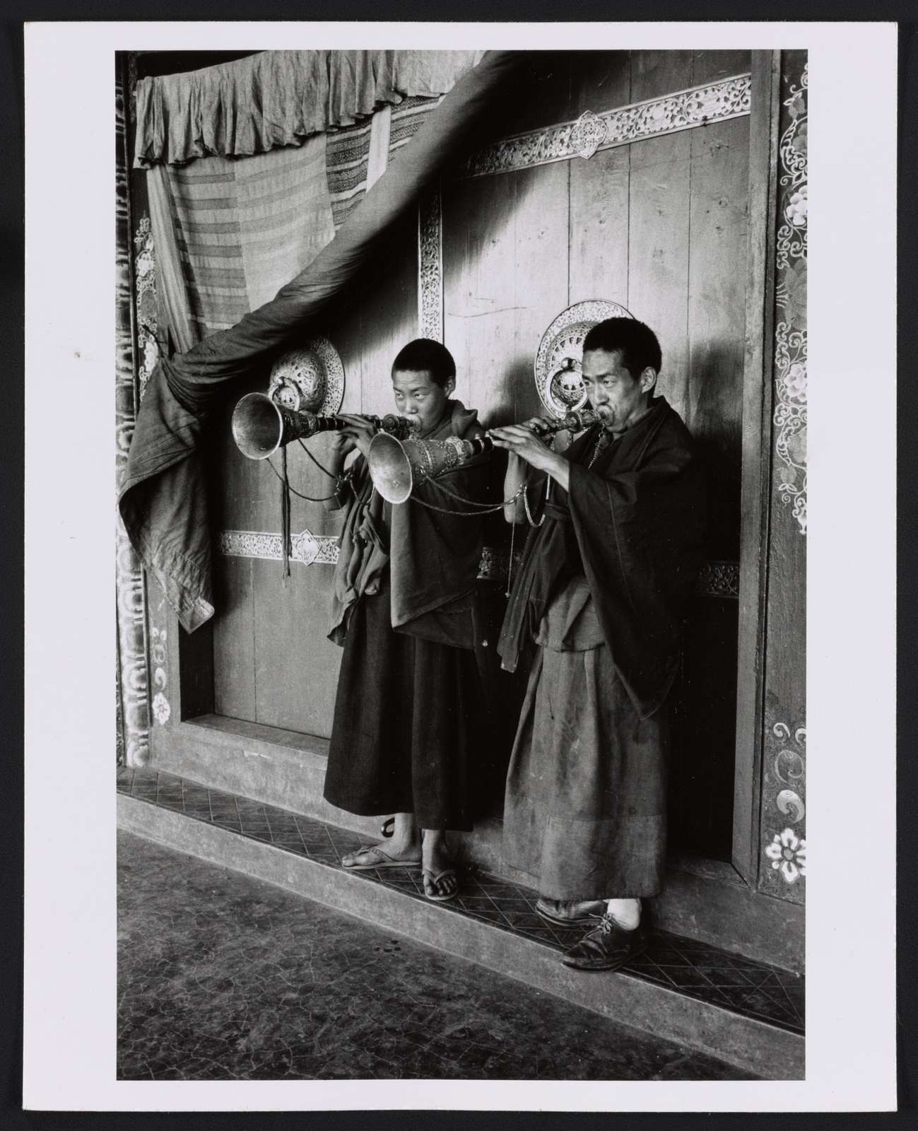 [Lamas blowing gyalings at temple door, Sikkim]