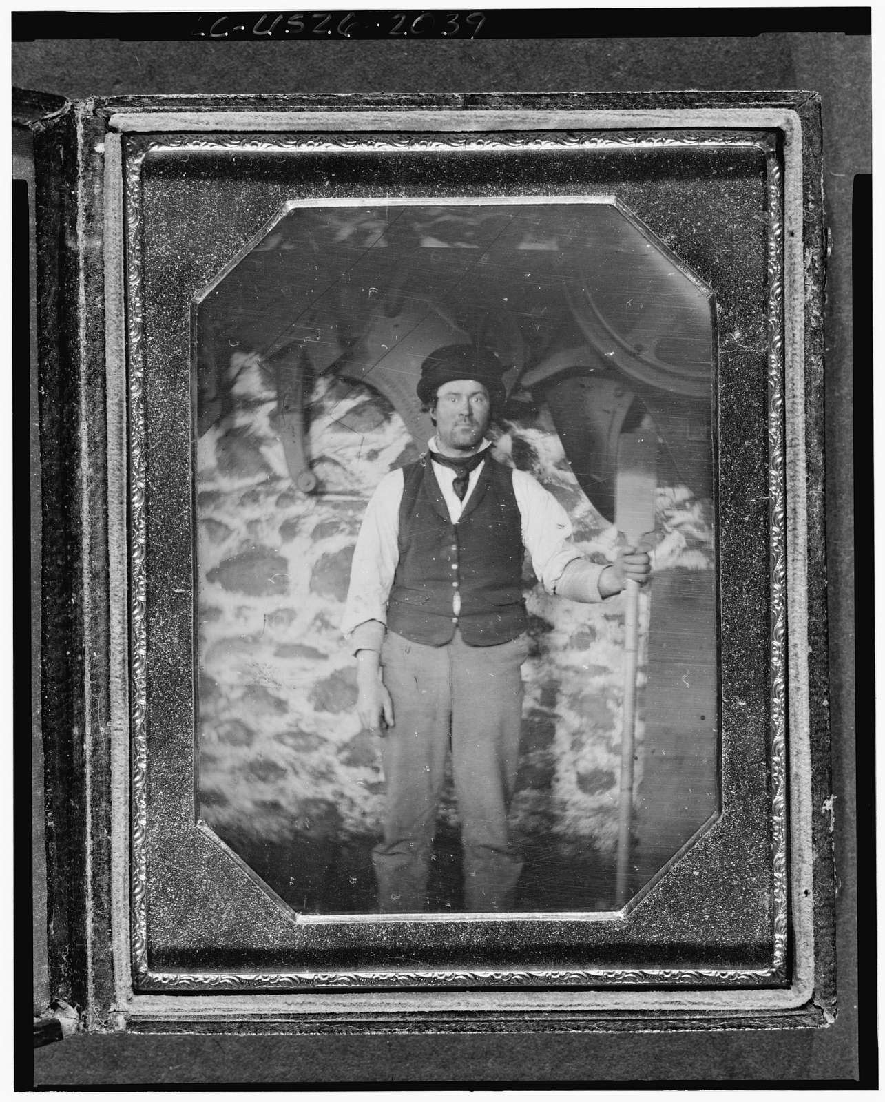[Occupational portrait of an unidentified man, full-length, facing front, with a long handled tool, in front of machinery and a stone wall]
