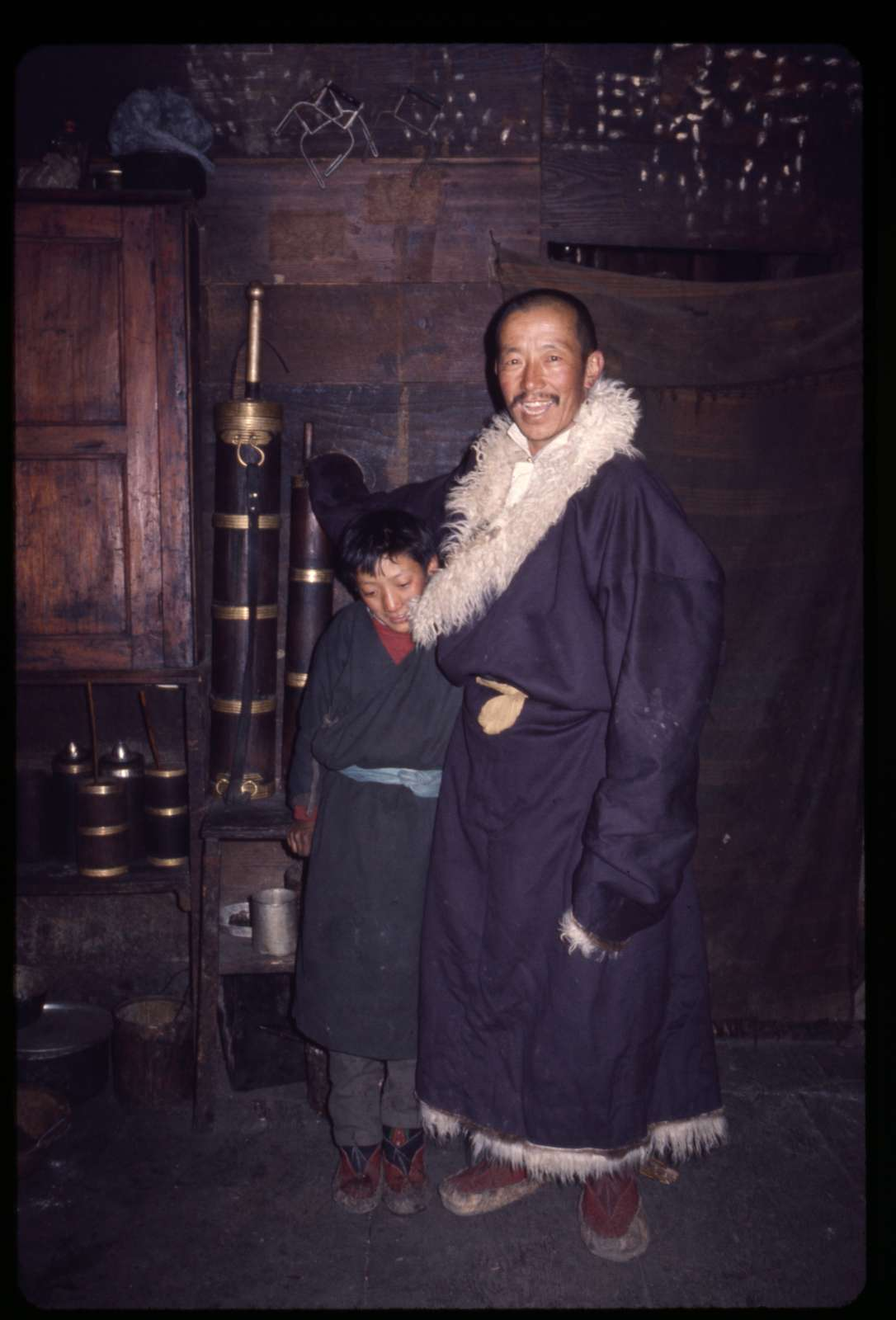 [Rinchen Namgyal Lachungpa and boy standing next to yak-butter churns, Lachung, Sikkim]