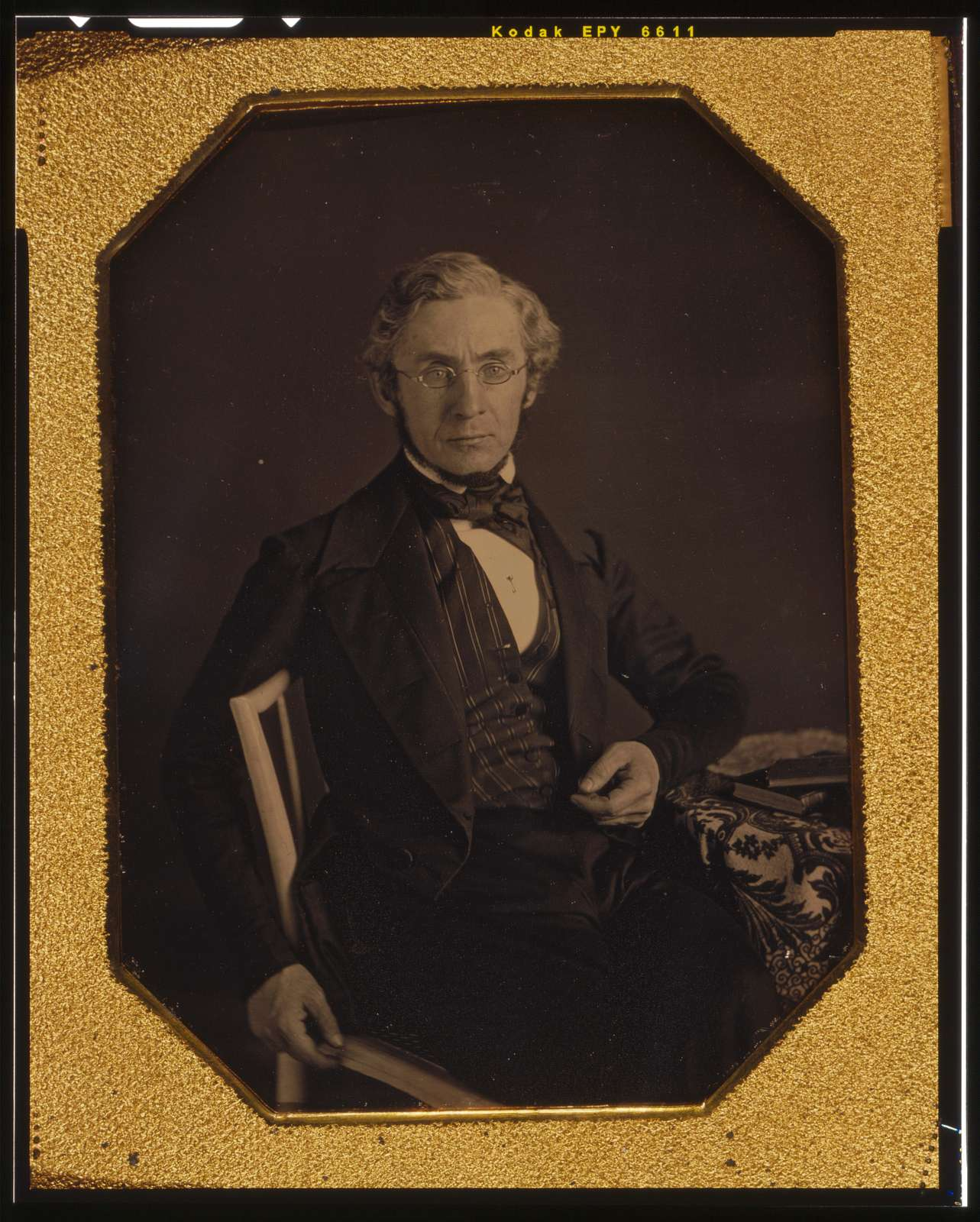 [William Young McAllister, three-quarters length portrait, seated in a chair, arm resting on table with tablecloth]