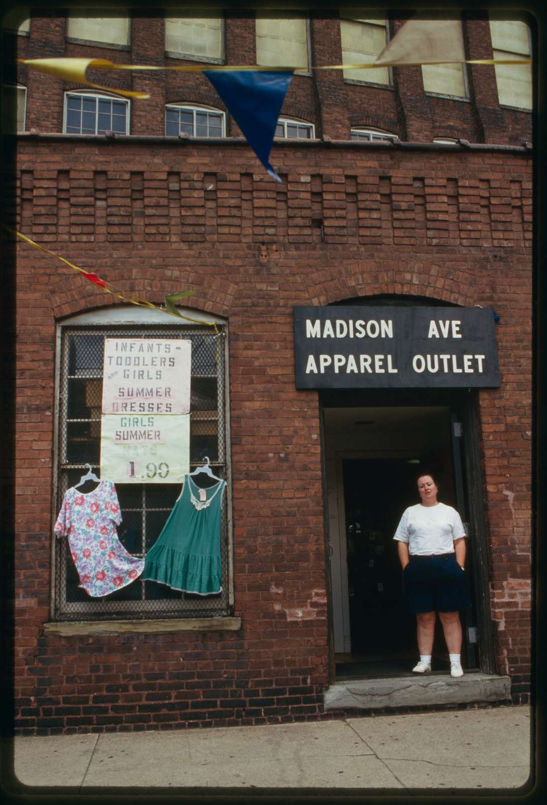 Exterior of Madison Apparel Outlet, 297 21st Avenue; worker stands in doorway.