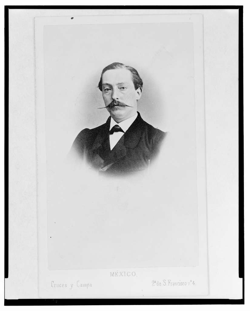 [Head-and-shoulders portrait of a man with handlebar mustache, facing front]